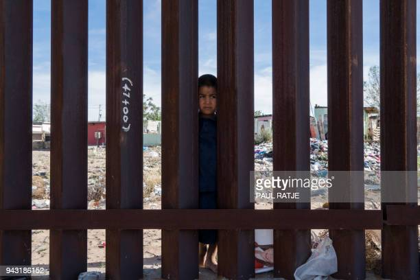 TOPSHOT A young Mexican boy is pictured peering from the Mexican side of the Border Fence in Anapra near El Paso Texas on Saturday April 7 2018 Days...