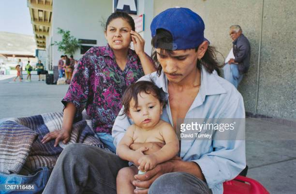 Young Mexican family, a man, woman and child, with the man holding the baby, on the border between Mexico and California in the United States, 1993.