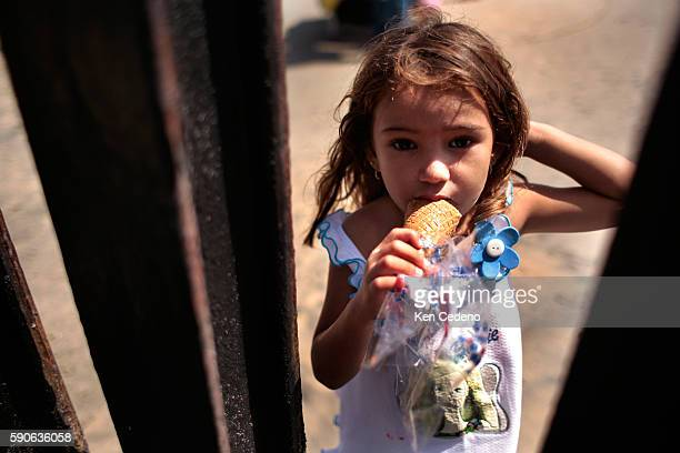 A young Mexican girl eats her ice cream bar at the border fence at Border Field State Park south of San Diego August 24 2006