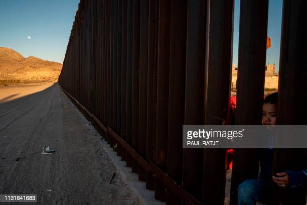 A young Mexican girl is pictured on the between the metal fencing on the USMexico border in Anapra New Mexico on March 19 2019 Speaking of an...