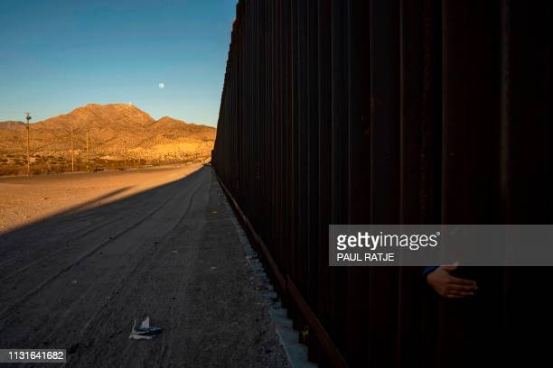 TOPSHOT A young Mexican girl's hand is pictured on the between the metal fencing on the USMexico border in Anapra New Mexico on March 19 2019...