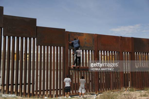 A young Mexican helps a compatriot to climb the metal wall that divides the border between Mexico and the United States to cross illegally to Sunland...