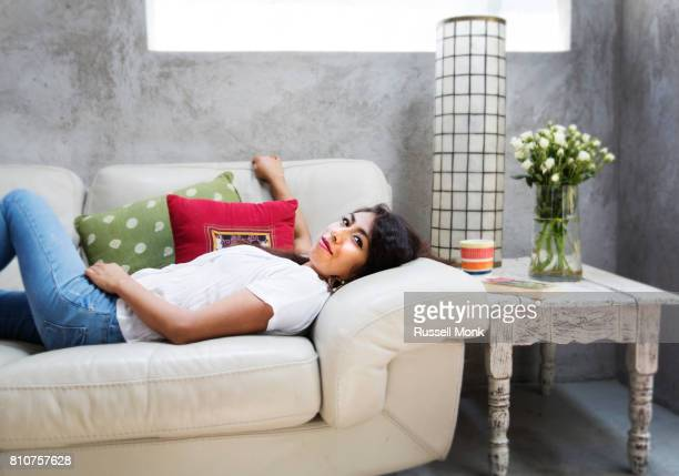 Young Mexican woman lying on a couch
