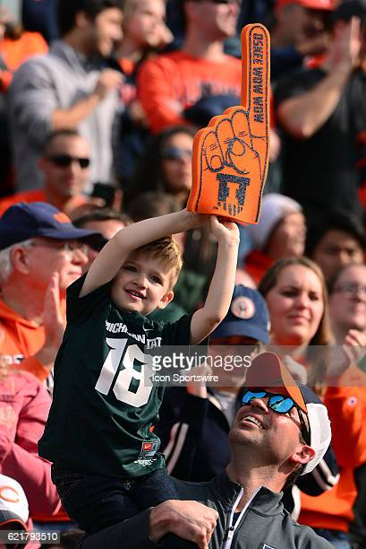 A young Michigan State Spartans fan switches his allegiance late in the game as he holds up an Illinois Fighting Illini foam finger during the Big...