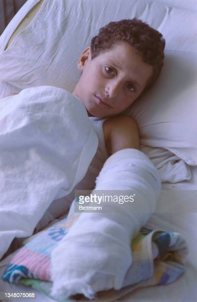 Young Middle Eastern boy lying in bed, his left arm heavily bandaged, in a hospital in an unspecified area of the West Bank, 1988.