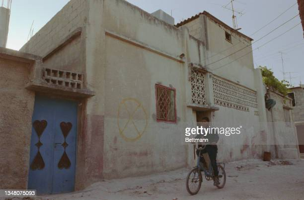 Young Middle Eastern boy riding a bicycle on a street, passing a building on which is a graffitied circle with a cross within, in an unspecified area...