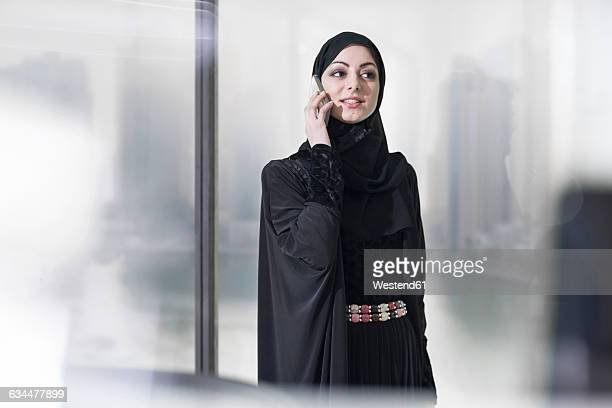 Young Middle Eastern businesswoman in office talking on the phone