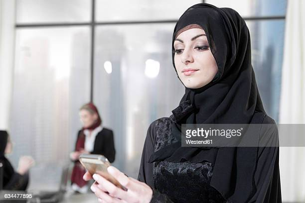 young middle eastern businesswoman in office using smart phone - traditional clothing stock pictures, royalty-free photos & images
