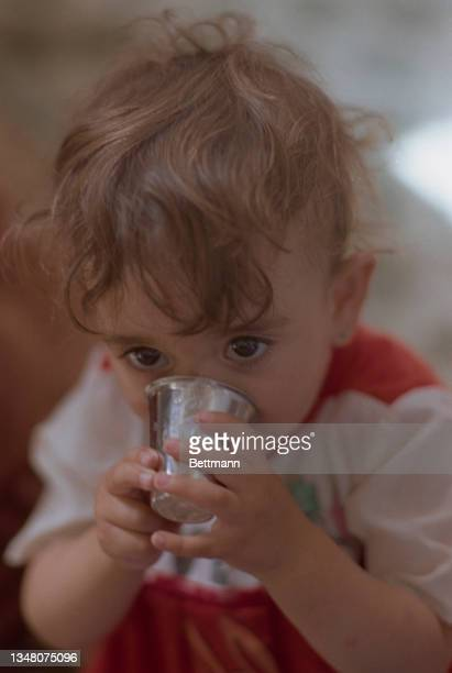 Young Middle Eastern child drinking from a small silver cup in an unspecified area of the West Bank, 1988.