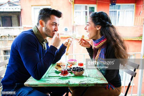 Young middle eastern couple enjoying Turkish snack on balcony