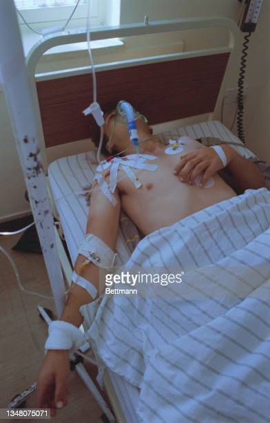 Young Middle Eastern man lying in bed, a cannula attached to his right arm, wearing an oxygen mask in a hospital in an unspecified area of the West...