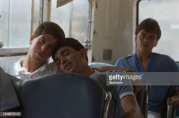 Young Middle Eastern men, each resting their head on the other, sit together on a bus, with a third man sitting on a seat behind, in Jerusalem,...