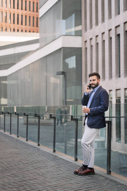 Young middle eastern professional with beard and elegant suit concentrated on mobile phone call conversation standing outdoors in modern corporate district
