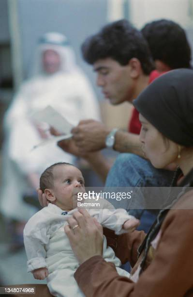 Young Middle Eastern woman wearing a black headscarf, holding a baby which is looking back at the woman, its mouth open, an unspecified area of the...