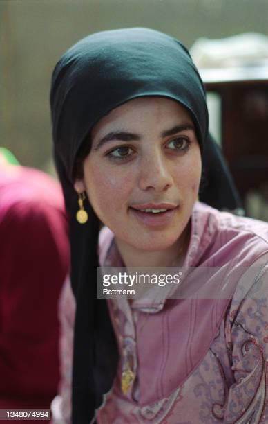 Young Middle Eastern woman wearing a pink outfit with lilac embroidery, a dark green headscarf and gold circular earrings, in an unspecified area of...