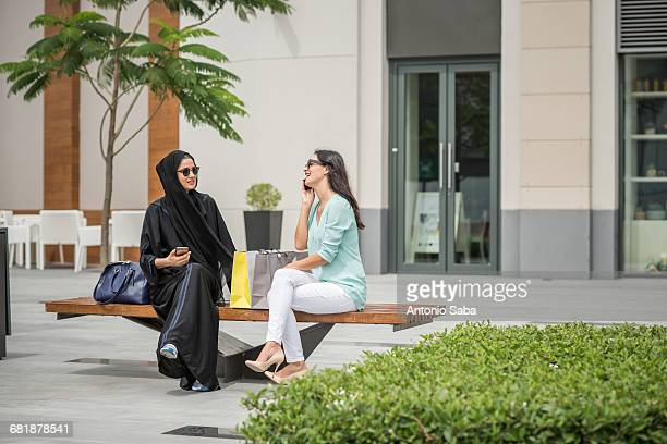 young middle eastern woman wearing traditional clothing sitting on bench with female friend, dubai, united arab emirates - female friendship stock pictures, royalty-free photos & images