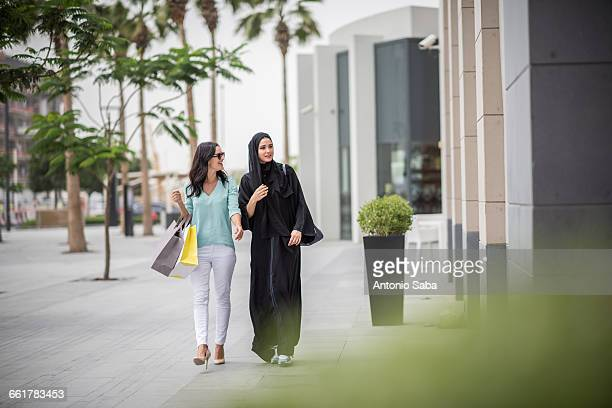 young middle eastern woman wearing traditional clothing walking along street with female friend, dubai, united arab emirates - shopping stock pictures, royalty-free photos & images