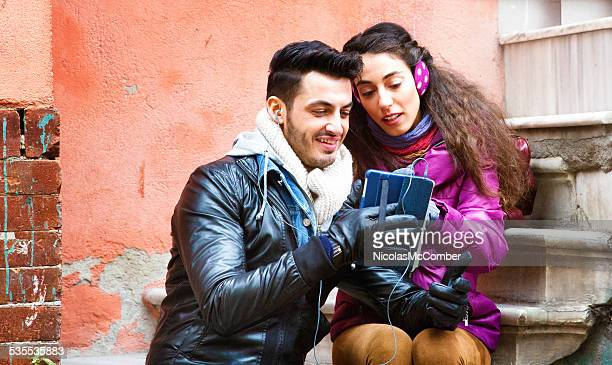 Young middle-eastern couple using tablet outdoors