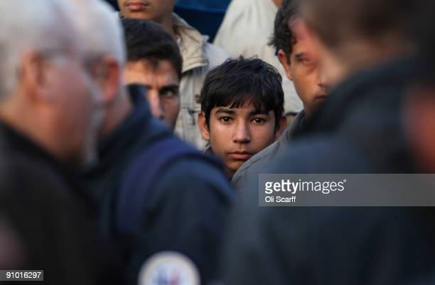 A young migrant awaits his removal by French police officers from the makeshift migrant camp known as 'The Jungle' adjacent to a ferry terminal to...
