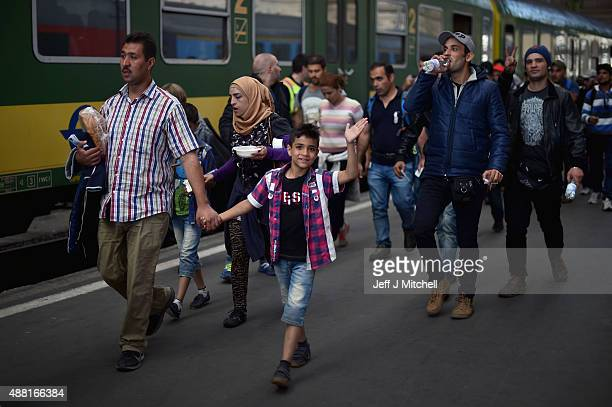 A young migrant boy waves as he prepares to board a train leaving for the Austrian border at the Keleti railway station on September 14 2015 in...