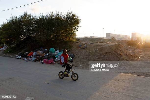 A young migrant cycles near the deserted specially outfitted shipping containers area for minors during the unaccompanied migrants minor evacuation...