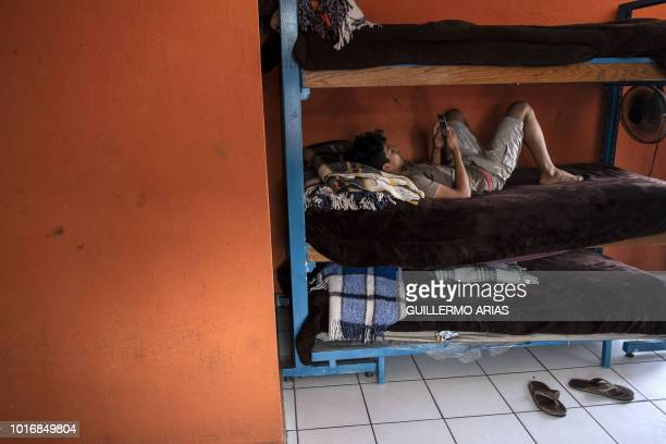 A young migrant from Honduras checks his phone as lies on his bed at Casas YMCA migrant minors shelter in Tijuana Baja California state Mexico on...