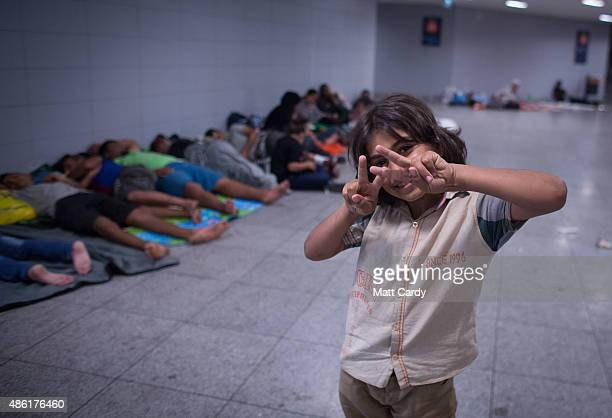 A young migrant girl poses for the camera as her family sleep in the transit zone of Keleti station in central Budapest on September 1 2015 in...