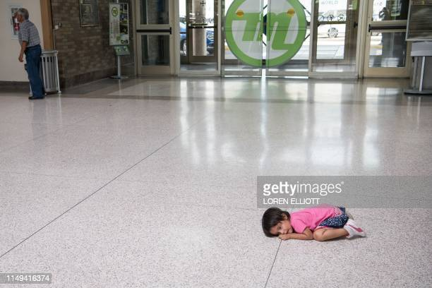 Young migrant girl sits on the floor as her father, recently released from federal detention with other Central American asylum seekers, gets a bus...