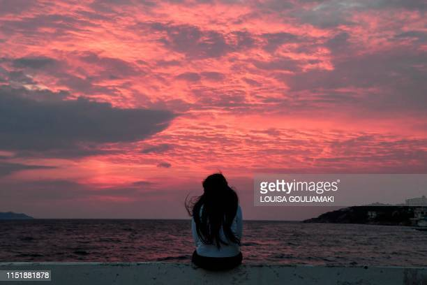 TOPSHOT A young migrant girl watches the sunset at the city of Vathy on the island of Samos early on June 18 2019 Less than two kilometres from the...