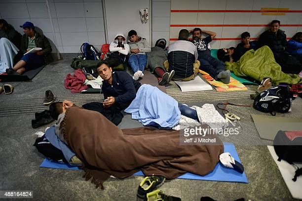 A young migrant man looks at the cameras as others rest near Keleti railway station as they wait to board trains leaving for the Austrian border on...