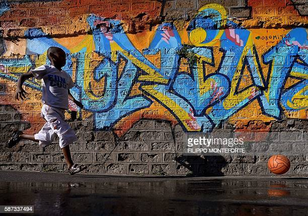 Young migrant runs after a ball in the street of Via Cupa outside the former Baobab migrants reception centre next to the Tiburtina train station in...