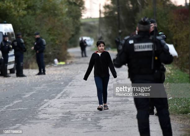 A young migrant walks past Gendarmes on October 23 2018 during an operation to evacuate a migrant camp in Grande Synthe northern France A migrant...