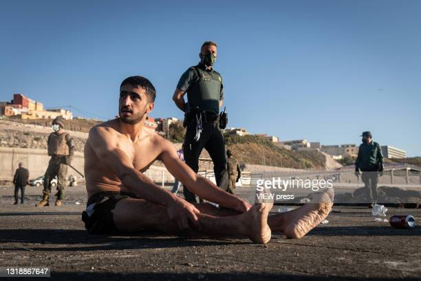 Young migrant who has crossed the border between Spain and Morocco by swimming along the Tarajal beach, waits, guarded by the army, to be returned to...