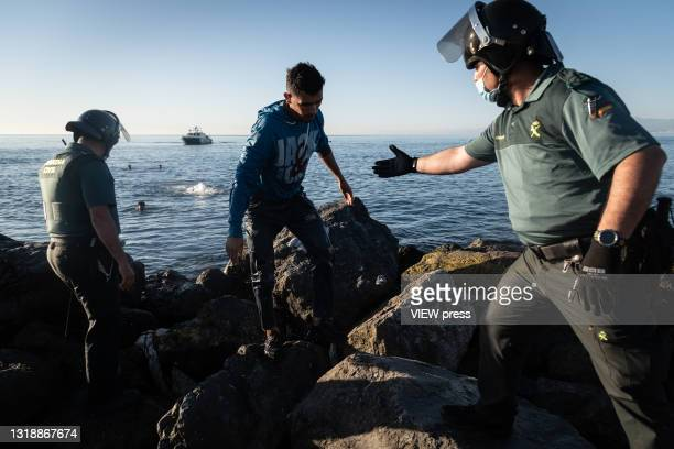 Young migrant who has crossed the border between Spain and Morocco by swimming along the Tarajal beach, steps out of the sea towards members of the...