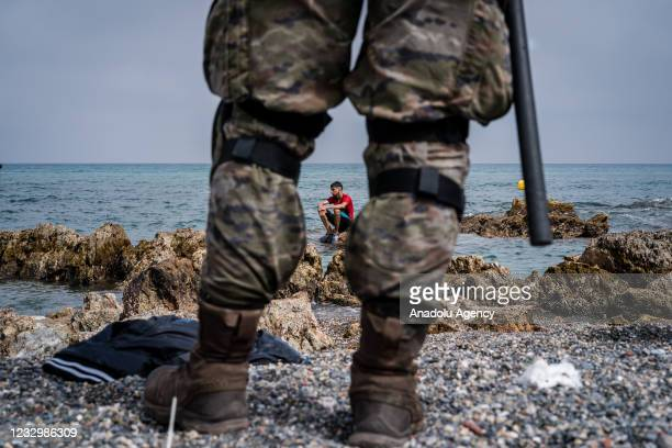 Young migrant who has just arrived swimming in Ceuta is watched by soldiers of the Spanish army, on May 19, 2021. Approximately 8 thousand migrants,...