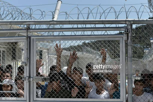 TOPSHOT Young migrants and refugees stand at a fence of the Moria detention center during a visit of Pope Francis in Mytilene on the Greek island of...