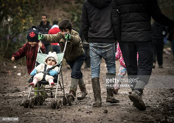 TOPSHOT Young migrants or refugees walk with a stroller on December 29 2015 in a camp in GrandeSynthe On December 28 2015 a migrant was found dead in...