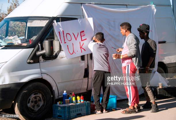Young migrants paint a sheet of paper with the lettering 'I love UK' in the 'Jungle' migrant camp in Calais northern France on October 31 during a...