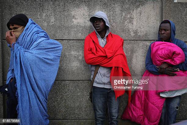 Young migrants wrap up warm for the night as French police clear the last remaining migrants from the main entrance and road into the Calais 'Jungle'...