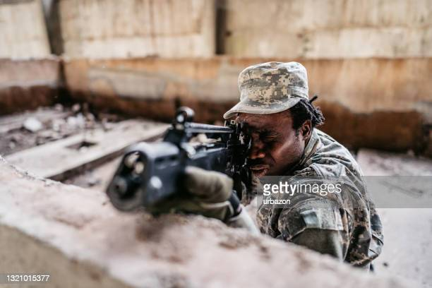 young military army soldier looks into gun sight and aims - military attack stock pictures, royalty-free photos & images