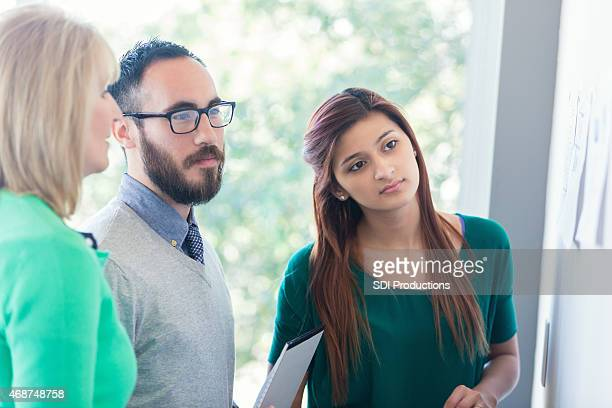 Young millenial business people examining project in modern bright office