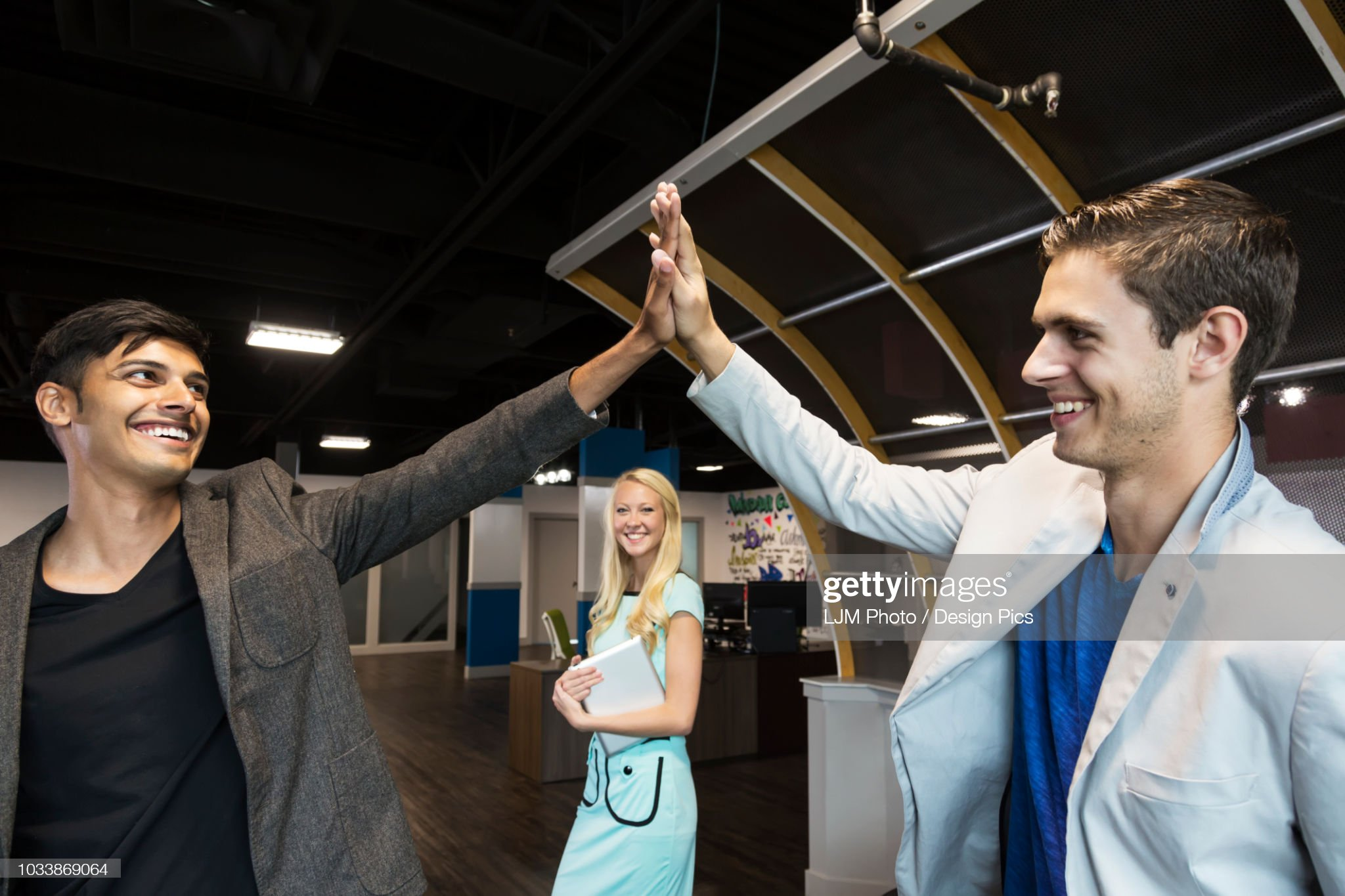Young millennial business co-workers celebrating a success with a high-five in the workplace : Stock Photo