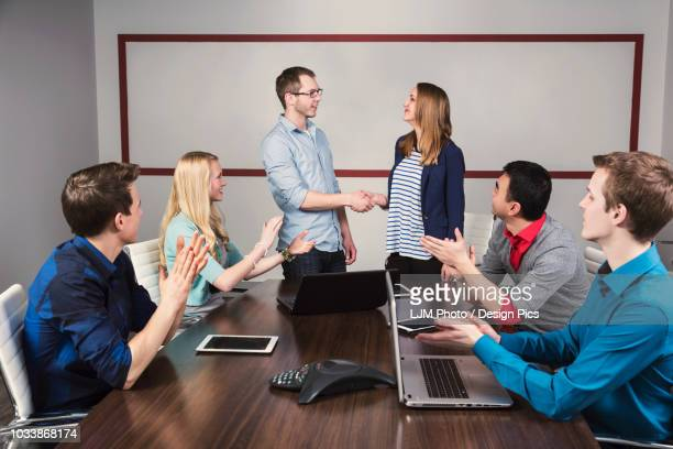 young millennial business professionals working together in a conference room in a place of business and praising the efforts of one of their peers - employee appreciation stock pictures, royalty-free photos & images