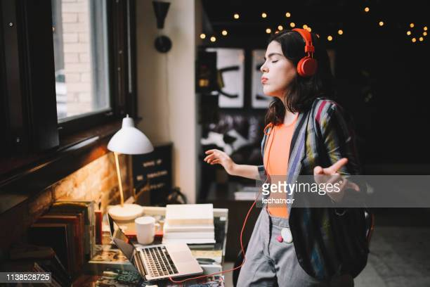 young millennial dancing to the music in her downtown los angeles apartment - dancing stock pictures, royalty-free photos & images