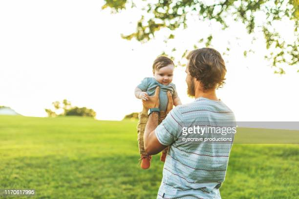 Young Millennial father enjoying time with his infant son at the Empire State Fair in Springfield MO on a hot July summer night
