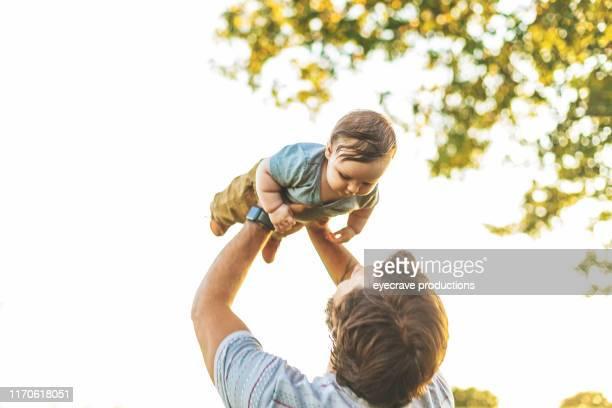 joven padre milenario disfrutando de tiempo con su hijo pequeño en la feria empire state en springfield mo en una noche caliente de verano de julio - adopción bebé fotografías e imágenes de stock