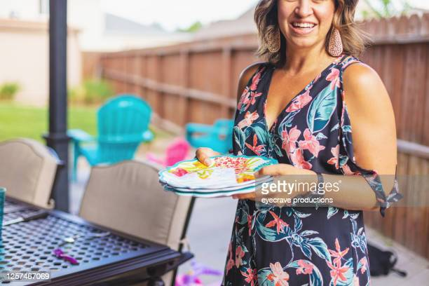 young millennial female setting patio dining table for cookout bbq photo series - eyecrave  stock pictures, royalty-free photos & images