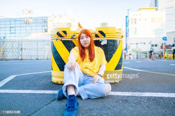 young millennial generation woman wearing yellow t-shirt and jeans sitting on asphalt - curvy asian woman stock pictures, royalty-free photos & images