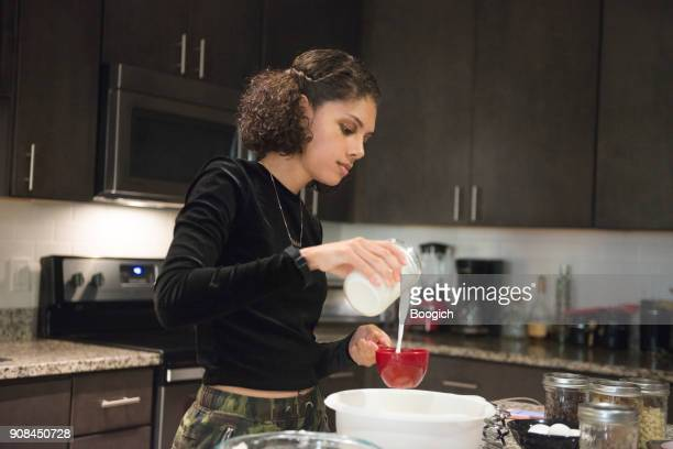 young millennial hispanic woman baking in home kitchen orlando usa - measuring cup stock pictures, royalty-free photos & images