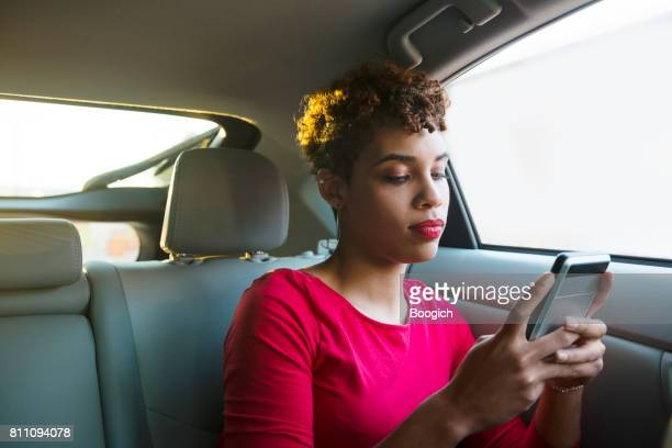 Young Millennial Mixed Black Woman Texting in Backseat Miami USA